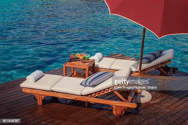 Sunshade and lounge chairs on a boardwalk, Dubrovnik, Croatia