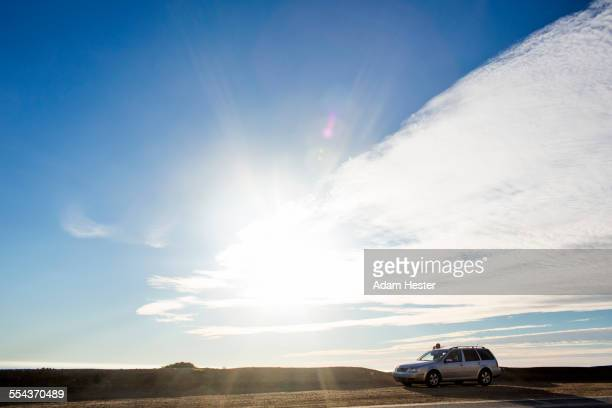 Sunshine and clouds over car on roadside
