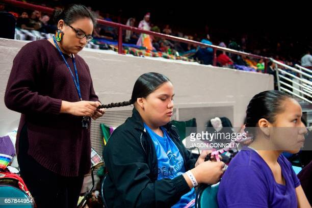 Sunshine Hayes braids her sister Skye's hair while Skye does the same for Ariana Hollow Horn prior to the start of the 43rd Annual Denver March...