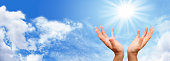 healer's hands outstretched with bright sunburst above on a blue sky and fluffy cloud background