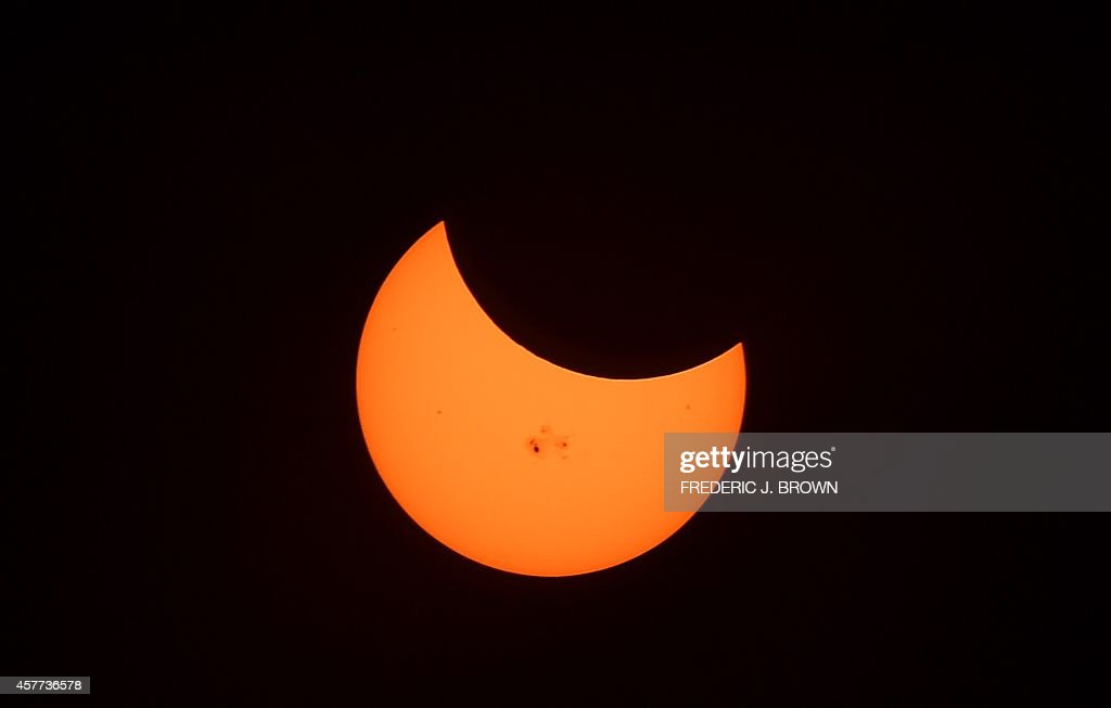 Sunspots are seen on the Sun as the Moon crosses during the peak moment at 327pm Pacific Time covering some 34 percent of the sun during a partial...