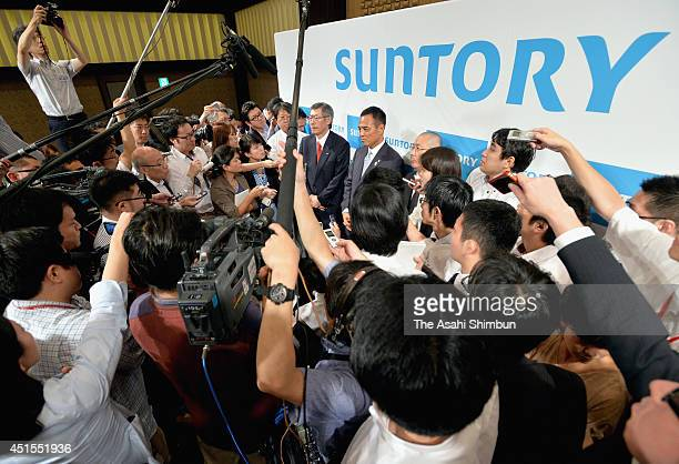Suntory Holding New President Takeshi Niinami and CEO Nobutada Saji area surrounded by media resporters after a press conference on July 1 2014 in...