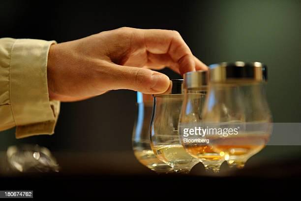 A Suntory Holdings Ltd's blender touches a glass of whisky at the company's Yamazaki distillery in Shimamoto Osaka Japan on Friday Sept 13 2013...