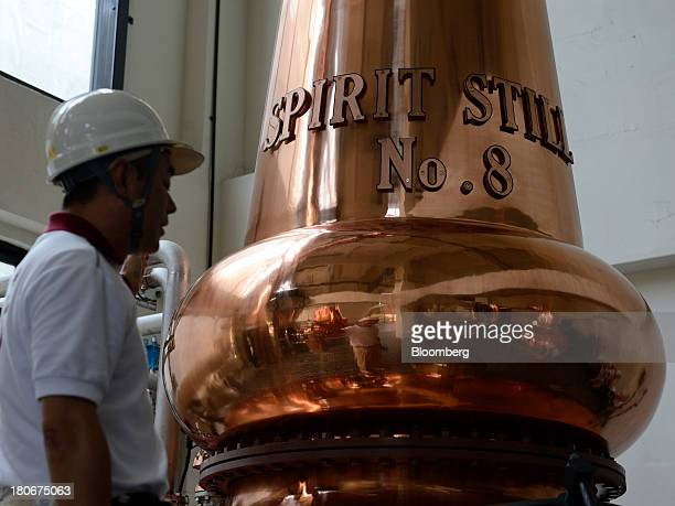 A Suntory Holdings Ltd's employee stands next to a still at the company's Yamazaki distillery in Shimamoto Osaka Japan on Friday Sept 13 2013 Suntory...
