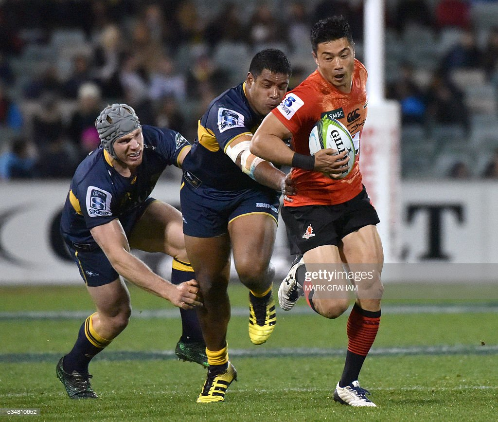 Sunwolves' Akihito Yamada (R) is tackled by Brumbies' David Pocock (L) and Scott Sio (C) during the Super Rugby match between Australia's ACT Brumbies and Japan's Sunwolves in Canberra on May 28, 2016. / AFP / MARK