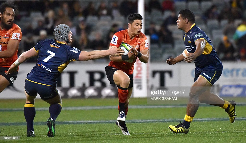 Sunwolves' Akihito Yamada (C) is tackled by Brumbies' David Pocock (L) and Scott Sio (R) during the Super Rugby match between Australia's ACT Brumbies and Japan's Sunwolves in Canberra on May 28, 2016. / AFP / MARK