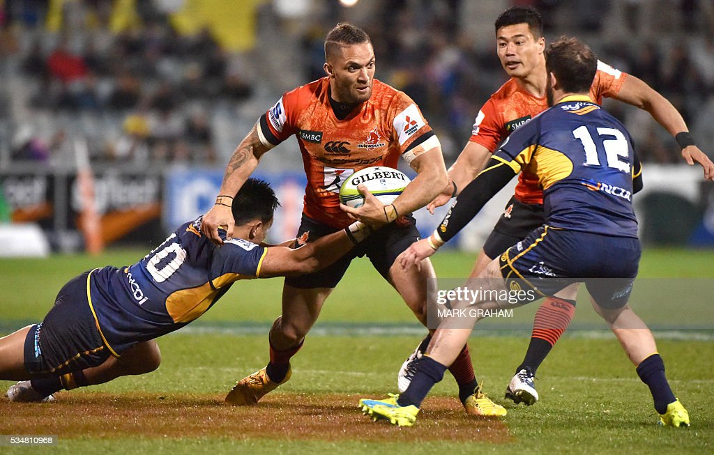 Sunwolves' Derek Carpenter (C) is tackled by ACT Brumbies' Christian Lealiifano (L) and Robbie Coleman (R) during the Super Rugby match between Australia's ACT Brumbies and Japan's Sunwolves in Canberra on May 28, 2016. / AFP / MARK