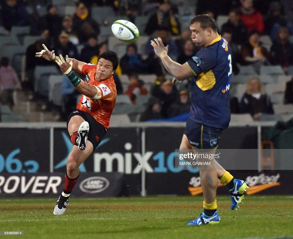 Sunwolves' Harumichi Tatekawa (L) kicks the ball in front of ACT Brumbies' Ruan Smith (R) during the Super Rugby match between Australia's ACT Brumbies and Japan's Sunwolves in Canberra on May 28, 2016. / AFP / MARK