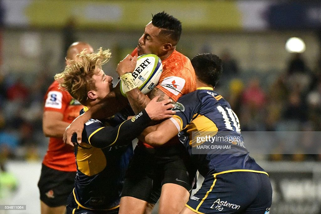 Sunwolves' Tusi Pisi (C) is tackled by ACT Brumbies' Jordan Jackson-Hope (L) and Christian Lealiifano (R) during the Super Rugby match between Australia's ACT Brumbies and Japan's Sunwolves in Canberra on May 28, 2016. / AFP / MARK