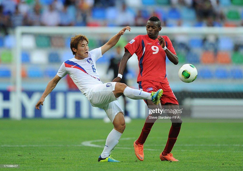 Sunwoo Kim of Korea Republic wins the ball from Maykel Reyes of Cuba during the Group B match between Cuba and Korea Republic at Kadir Has Stadium on June 21, 2013 in Kayseri, Turkey.