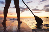 paddle board on the beach, close up of standing  legs and paddle