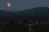 Moon rises above the Dragoon mountains leading up to the super blood moon shot in Tombstone Arizona  on September 27 2015.
