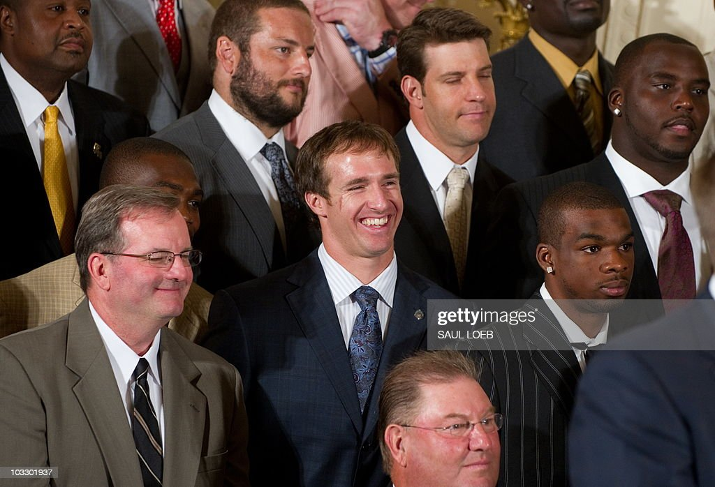 Super Bowl MVP Drew Brees (C) laughs as US President Barack Obama speaks during an event honoring the 2010 Super Bowl Champion New Orleans Saints in the East Room at the White House in Washington, DC, August 9, 2010. AFP PHOTO / Saul LOEB