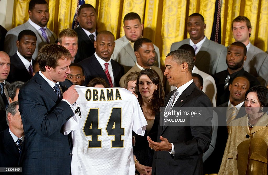 Super Bowl MVP Drew Brees (L) presents US President Barack Obama with a jersey during an event honoring the 2010 Super Bowl Champion New Orleans Saints in the East Room at the White House in Washington, DC, August 9, 2010. AFP PHOTO / Saul LOEB