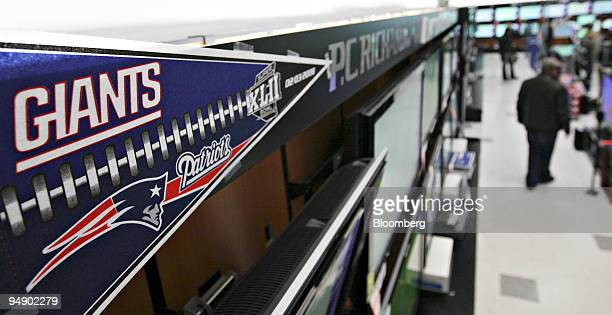 Super Bowl XLII pennant hangs above a row of flatscreen televisions inside a PC Richard Sons store in New York US on Thursday Jan 31 2008 With...