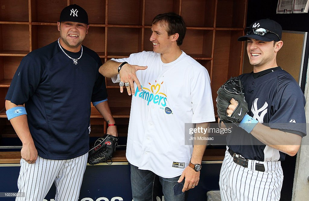 Super Bowl XLIV MVP Drew Brees of the New Orleans Saints shows off his championship ring and a 2009 New York Yankees World Series ring with Joba Chamberlain #62 and David Robertson #30 of the Yankees prior to the game against the New York Mets on June 20, 2010 at Yankee Stadium in the Bronx borough of New York City.