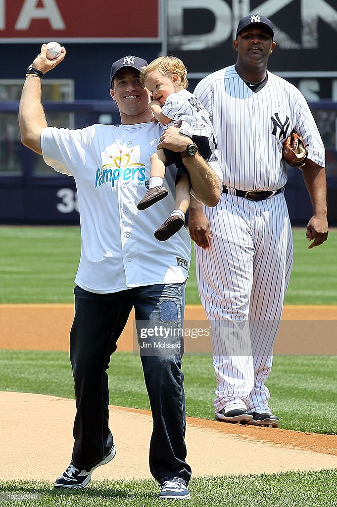 Super Bowl XLIV MVP Drew Brees of the New Orleans Saints, with his son Baylen, throws out the ceremonial first pitch as CC Sabathia #52 of the the New York Yankees looks on prior to the game against the New York Mets on June 20, 2010 at Yankee Stadium in the Bronx borough of New York City.