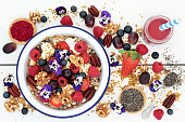 Super food healthy breakfast concept with edible viola flowers, acai berry smoothie and powder, fruit, granola, yoghurt, nuts, chia seed and pollen grain, high in protein, omega 3, antioxidants, miner