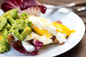 Very healthy high fat low carb (keto or ketogenic) breakfast consisting of three fried eggs, a whole avocado, radicchio salad leaves, organic bacon and lots of olive oil. Not only does this breakfast
