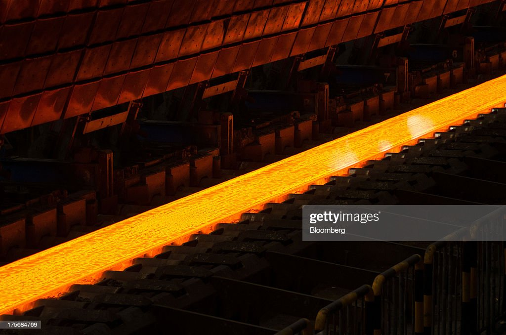 A super heated steel bar moves along the production line in the hot strip shop at the ArcelorMittal Poland SA steel mill in Krakow, Poland, on Tuesday, Aug. 6, 2013. ArcelorMittal, the biggest steelmaker globally and in Poland, said on March 15 it expects European demand to slide before rebounding in 2014. Photographer: Will Boase/Bloomberg via Getty Images