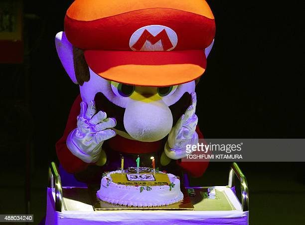 'Super Mario' blows out the candles on a cake during celebrations and a live performance of the most wellknown Mario music to mark the game's 30th...