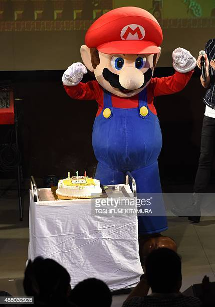 'Super Mario' poses after blowing out the candles on a cake during celebrations and a live performance of the most wellknown Mario music to mark the...