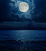 super moon in dark clouds over sea