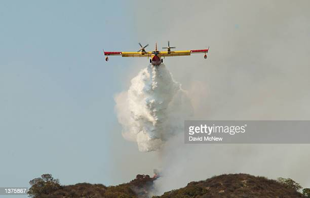 CL215 'Super Scooper' air tanker drops a white cloud of water instead of the usual red fire retardant used by other air bombers at a wildfire...