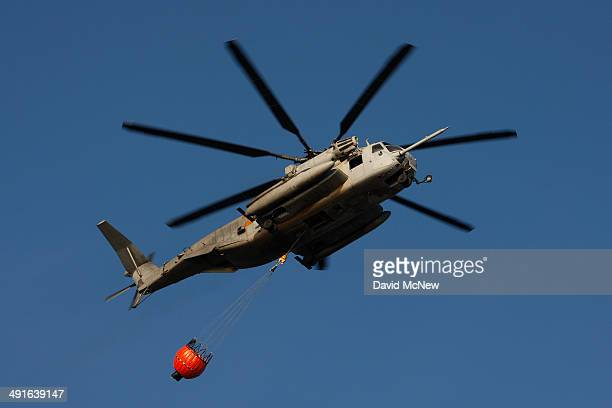 Super Stallion Marine helicopter flies over Tressles surf beach with an empty bucket to scoop water from the ocean to fight the Talega Fire on nearby...