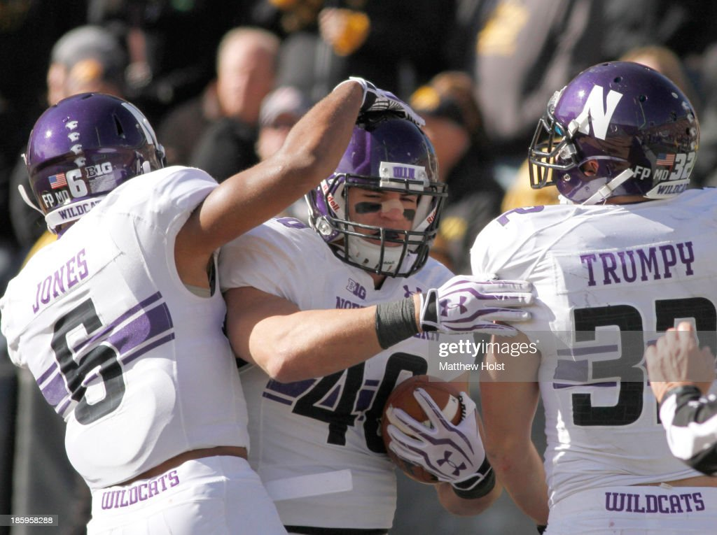 Superback Dan Vitale #40 of the Northwestern Wildcats celebrates with wide receiver Tony Jones #6 and running back Mike Trumpy #32 after scoring a touchdown during the third quarter against the Iowa Hawkeyes on October 26, 2013 at Kinnick Stadium in Iowa City, Iowa. Iowa won 17-10.