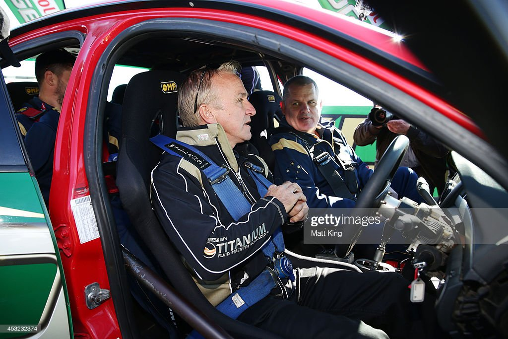 Supercar driver Russell Ingall talks to Wallabies coach Ewen McKenzie in his V8 Supercar during an Australian Wallabies media session at Mount...