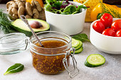 Superfoods and homemade salad dressing vinaigrette with mustard, honey, balsamic vinegar and olive oil on a stone or slate background.