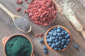 Bowls of superfoods on the wooden background: top view