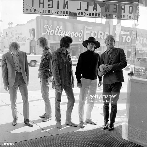 Supergroup 'Buffalo Springfield' perform pose for a portrait outside a movie theatre in 1966 in Hollywood California Stephen Stills Bruce Palmer Neil...