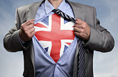 Businessman in classic superman pose tearing his shirt open to reveal t shirt with the British union jack flag concept for european referendum, patriotism, freedom and national pride