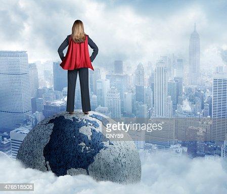 Superhero Businesswoman Standing On Globe