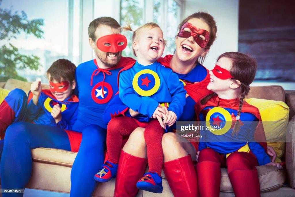Superhero family laughing on sofa