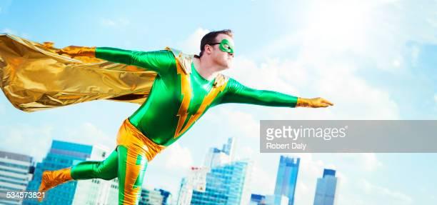 Superhero flying on city rooftop