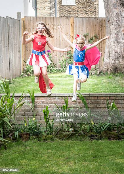 Superhero girls leaping off wall in garden