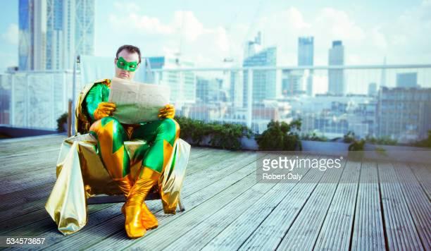 Superhero reading newspaper on city rooftop