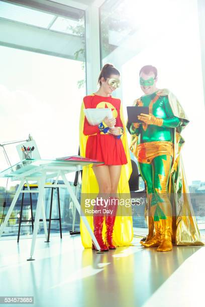 Superheroes working with digital tablet in office