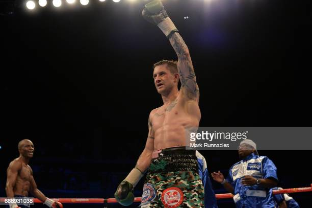 SuperLightweight World Champion Ricky Burn holds his arm aloft at the end of the bout with IBF/IBO SuperLightweight World Champion Julius Indongo...