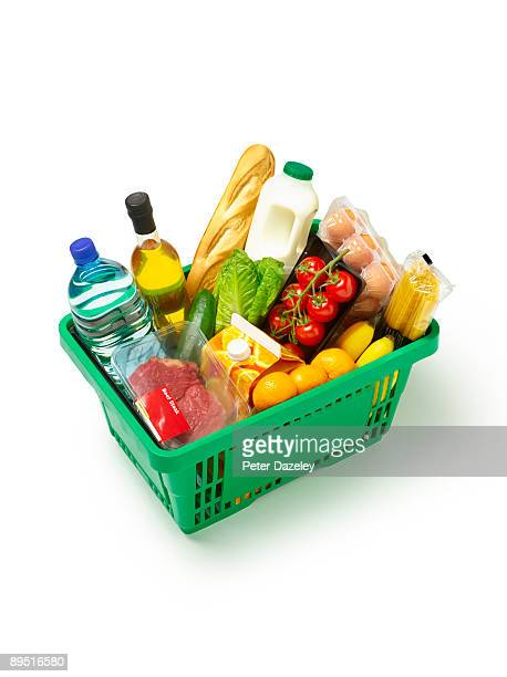 Supermarket basket with organic produce on white.