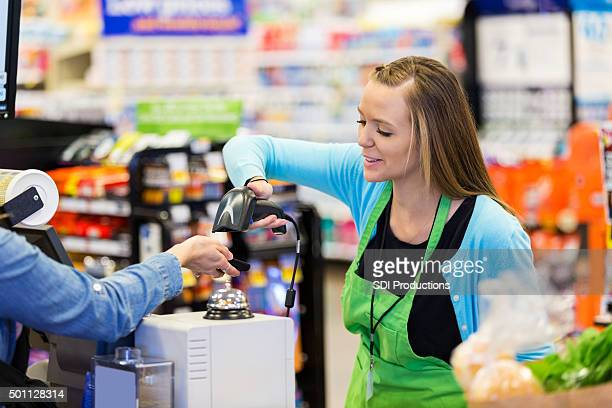 Supermarket cashier scanning smart phone to accept payment or coupons