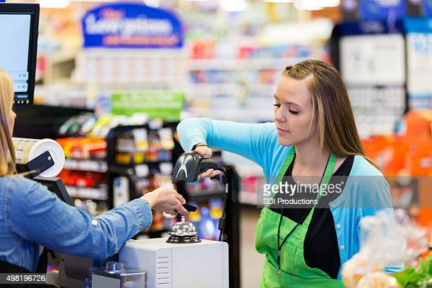 Supermarket cashier scanning smart phone to accept payment