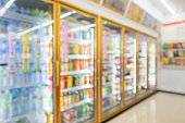 supermarket convenience store refrigerators with soft drink bottles on shelves abstract blur background