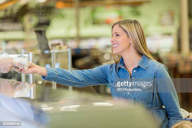 Supermarket customer purchasing deli meat from counter