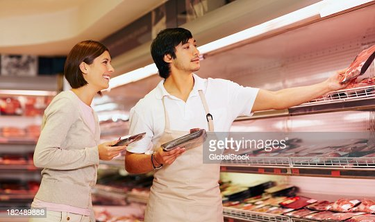 Supermarket employee helping a female pick packet of meat