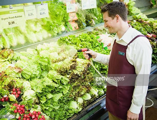 Supermarket Employee Spraying Produce