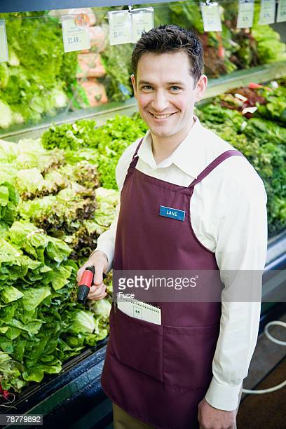 Supermarket Employee Spraying Produce
